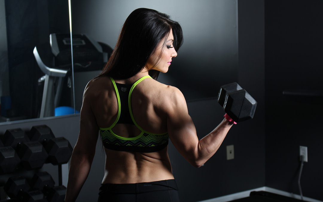 female personal trainer doing dumbbell curls