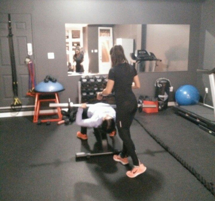 personal trainer spotting client at boutique studio