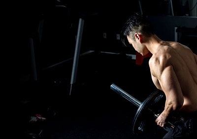 fit asian personal trainer doing bent over rows with landmine