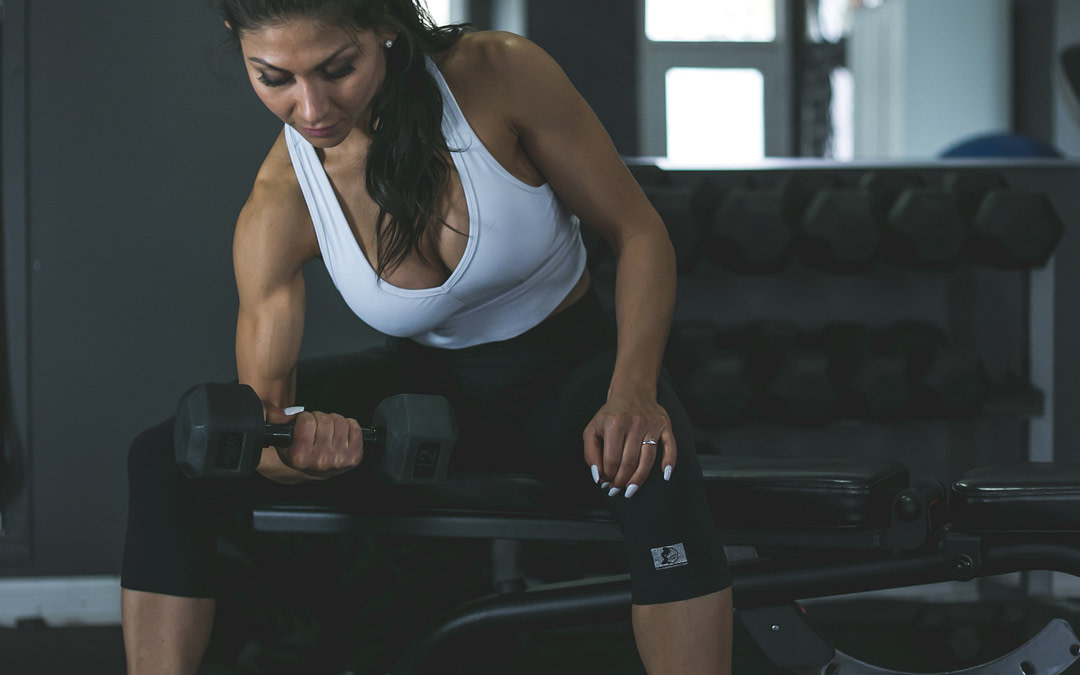 claudia personal trainer doing single arm bicep curls